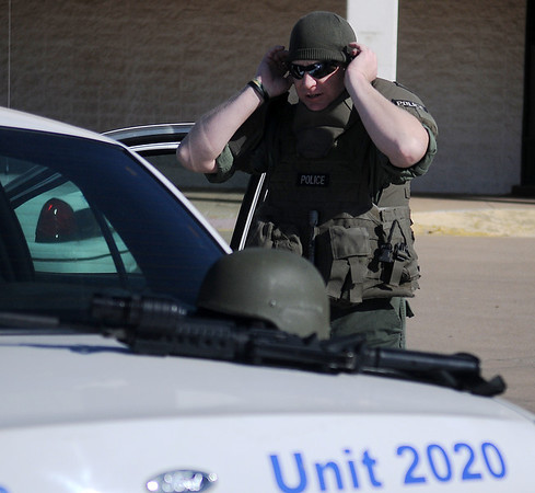 Enid Police officer, Randall Wilson, prepares for a new recruitment video at Homeland Wednesday, March 13, 2013. When KJ Productions and the Enid Police arrived at Homeland, one of the entrance doors to the building was open, so officers secured the area and cleared the building before filming could begin. (Staff Photo by BONNIE VCULEK)
