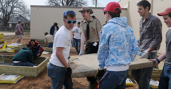 Makay Tobler (standing back, second from left) carries a slab of concrete with the help of members of his scout Troop 17 and Enid High School Community Service Club Saturday, March 16, 2013. Tobler received grant money from Northwest Osteopathic Association, Rotary International and AMBUCS to build gardening beds for Loaves and Fishes as his Eagle Scout project. (Staff Photo by BONNIE VCULEK)