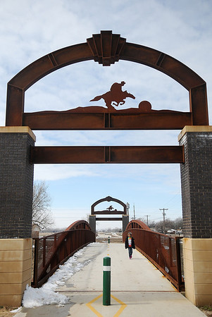 An elementary student crosses the Enid Trails bridge near Meadows Point Apartments Saturday, March 2, 2013. The new trails are used by avid runners and walkers throughout Enid. (Staff Photo by BONNIE VCULEK)