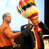 The National AMBUCS President Kent Clingenpeel, from Enid, adjusts his head dress after Enid Noon AMBUCS President, Eli Berry, makes the Nee SKA-TUNGA-GAWHEGA (Chief of Civic Leaders) presentation to Clingenpeel during a luncheon at Northern Oklahoma College Friday, March 22, 2013. (Staff Photo by BONNIE VCULEK)