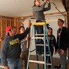 Marquette students hang sheetrock inside the garage of a Habitat for Humanity home at 2001 E. Maple Wednesday. Eighteen students are giving  up their spring break to help build the new home for an Enid family. (Staff Photo by BONNIE VCULEK)