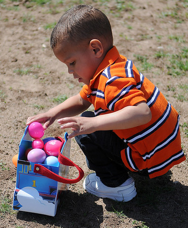 Tavin Ware fills his Thomas the Train basket during Sandbox Learning Center's Easter egg hunt Saturday, March 30, 2013. The center's employees and Northwestern Oklahoma State University Psychology Club members filled thousands of eggs with candy for the children. (Staff Photo by BONNIE VCULEK)