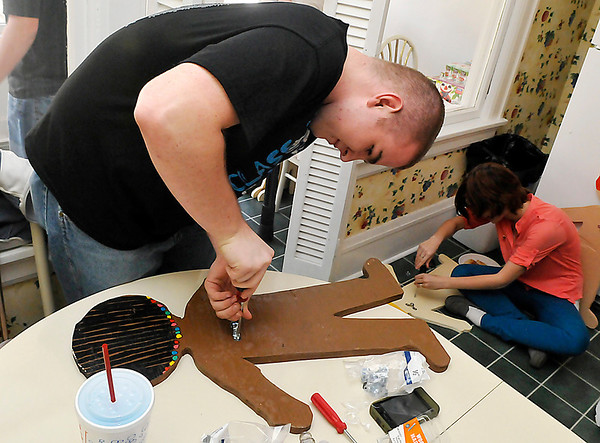 """Enid AFJROTC members, Tucker Singleton and Jenii Robertson attach brackets to wooden """"children"""" Monday at the  Garfield County Child Advocacy Center. (Staff Photo by BILLY HEFTON)"""