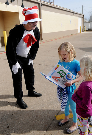 The Cat in the Hat, portrayed by Evan Chermack, presents Kyndall and Ryan Thornberry with Dr. Seuss's ABC book at Loaves & Fishes Wednesday, March 6, 2013. The girls were the first to spot Cat in the Hat to win their special prize. (Staff Photo by BONNIE VCULEK)