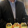 Neil Juhnke, COO of Northstar Agri Industries, pauses by bottles of the company's limited edition canola oil at the Convention Hall Junior Ballroom Thursday, March 28, 2013. (Staff Photo by BONNIE VCULEK)