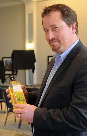 Neil Juhnke, COO of Northstar Agri Industries, holds a bottle of the company's limited edition canola oil at the Convention Hall Junior Ballroom Thursday, March 28, 2013. (Staff Photo by BONNIE VCULEK)