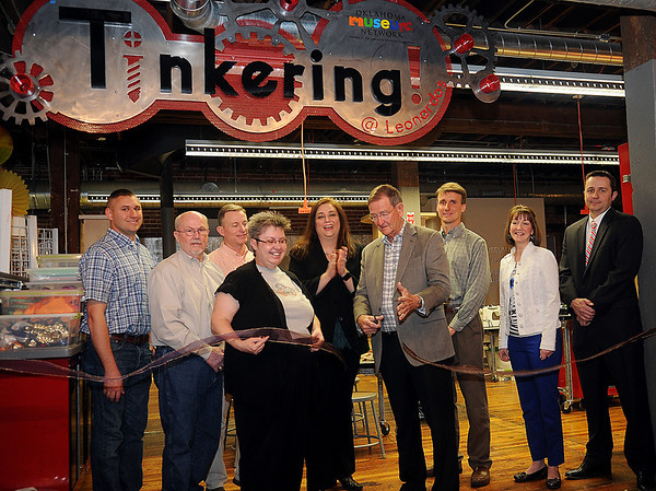 Enid Mayor Bill Shewey officially cuts the ribbon during the grand opening of the new Tinkering exhibit at Leonardo's Discovery Warehouse Friday, March 15, 2013. The Oklahoma Museum Network permanent exhibit was funded by Donald W. Reynolds Foundation. (Staff Photo by BONNIE VCULEK)