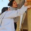 Kelsey Calemba and Andrea Spagnoli check a wood trim measurement on a new Habitat for Humanity home at 2001 E. Maple Wednesday, March 13, 2013. Eighteen Marquette students gave up their spring break to help build the home for an Enid family. (Staff Photo by BONNIE VCULEK)