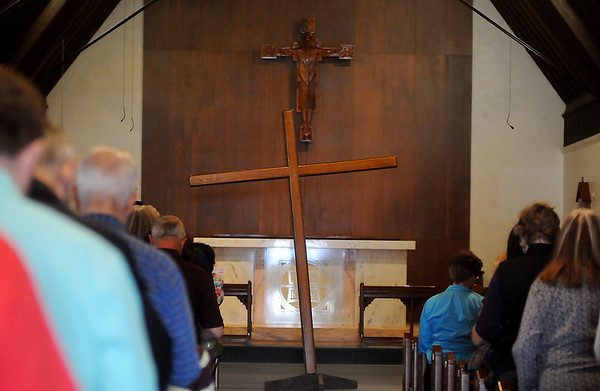 Clergy and members of several Enid churches gather inside St. Matthews Episcopal Church as they observe the passion and death of Jesus on Good Friday, March 29, 2013. During the service, participants processed with a wooden cross from the United Methodist Church, to St. Matthews Episcopal Church into St. Francis Xavier Catholic Church before sharing a Lenten meal. (Staff Photo by BONNIE VCULEK)