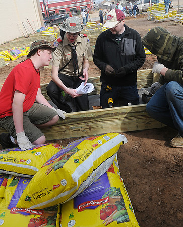 Makay Tobler (second, from left) discussses his Eagle Scout project with Jackson Crockett (left) Jeremy Phelps and Ashton Clemons as they build gardening beds for Loaves and Fishes Saturday, March 16, 2013. (Staff Photo by BONNIE VCULEK)