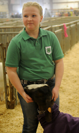 Abbi John holds her boer goat, Buster, during the Northwest District Junior Livestock Show at the Chisholm Trail Expo Center Thursday, March 7, 2013. John, a fifth-grade student in the Chisholm 4-H Club, was preparing her 81 lb. wether for the show ring. (Staff Photo by BONNIE VCULEK)