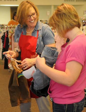 Deborah Gungoll assists a customer with a purchase during Grace World Outreach Church's My Child To Yours consignment sale Friday, March 15, 2013. (Staff Photo by BONNIE VCULEK)