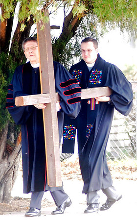 Dr. Grayson Lucky, from United Methodist Church, and Rev. Andrew Long, from First Presbyterian Church, carry a wooden cross as clergy and members of several Enid churches observe the Passion and Death of Jesus on Good Friday, March 29, 2013. Dr. Lucky and Rev. Susan Southall from the United Methodist Church, David Hume and Missioner Lissa Qualls from St. Matthews Episcopal Church, Rev. Joseph Irwin, Rev. Rajesh Mankena and Deacon Tony Crispo, with St. Francis Xavier Catholic Church, and Rev. Long, from the First Presbyterian Church officiated during the event. (Staff Photo by BONNIE VCULEK)