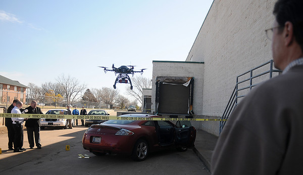 A remote helicopter camera operated by Jack Quirk (right) from KJ Productions, films a new Enid Police Department recruitment video at the vacant Homeland location Wednesday, March 13, 2013. (Staff Photo by BONNIE VCULEK)