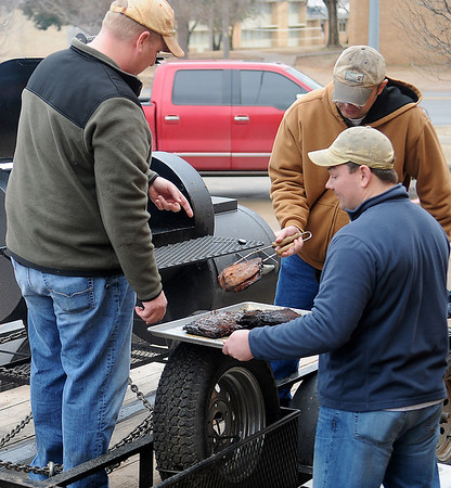 Enid Noon Ambucs' Drew Ewbank, Dalen McVay and Robbie Bullis remove slabs of ribs from the smoker during the Kansas City Barbeque Society BBQ judging class at Northern Oklahoma College-Enid Gantz Center Saturday, March 9, 2013. (Staff Photo by BONNIE VCULEK)