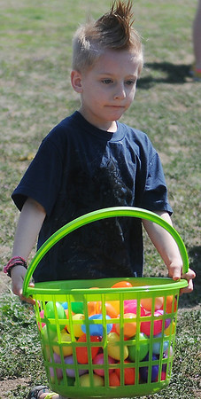 A young boy carries an egg-filled basket during Sandbox Learning Center's Easter Egg Hunt Saturday, March 30, 2013. (Staff Photo by BONNIE VCULEK)