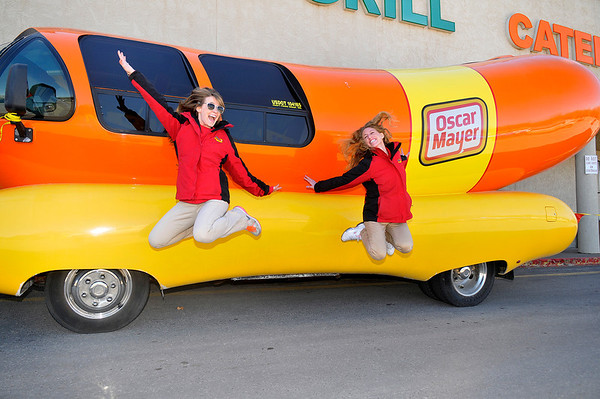 Hotdoggers, Hannah Carlson (left) and Molly Segall take a leap next to the Oscar Meyer Wienermobile Thursday at Jumbo's West. (Staff Photo by BILLY HEFTON)