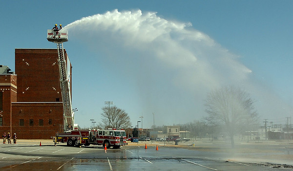 Enid Fire Department sprays the parking lot west of Convention Hall during training on the ladder truck Tuesday. (Staff Photo by BILLY HEFTON)