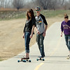 Lauren Passey, Ted Matthews and Jessica Passey ride longboards on the Enid Trail Wednesday between Oakwood and Cleveland streets. (Staff Photo by BILLY HEFTON)