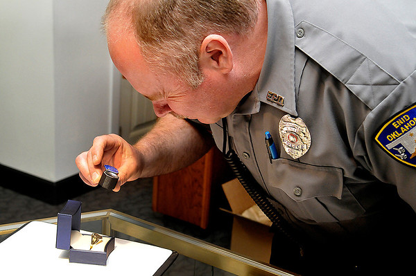 Enid police officer, Mike Evans, uses a loop to view a coustom made ring he recieved from Jackson Diamond Jewelers for being named Officer of the Year. (Staff Photo by BILLY HEFTON)