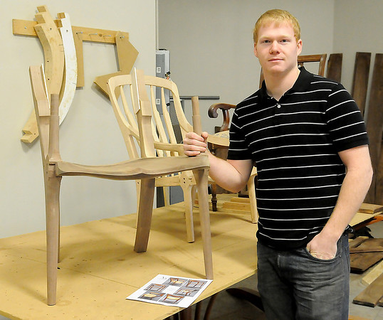 Joe Lamerton, a local custom woodworker, pauses next to a low back chair that he is creating in his shop at the James W. Strate Center for Business Development Friday, March 7, 2014. Lamerton has been participated in the incubator program for the past few months. (Staff Photo by BONNIE VCULEK)