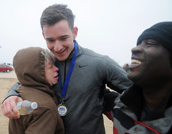 Michael Bartel receives congratulations from Yes We Can Civitan Club members after he wins the 5K run during the 7th annual Warren Edds Memorial Civitan Chiller Challenge at Crosslin Park Lake Saturday, March 1, 2014. Bartel, an OSS Radar Approach Control operator, is stationed at Vance Air Force Base. Proceeds from the event support special olympics track and field events each year. (Staff Photo by BONNIE VCULEK)