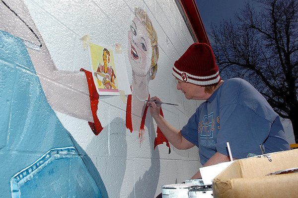 Pam Gilbreath, art teacher at Waller Middle School, paints a mural on the side of C & C Dry Cleaners on south Van Buren Thursday. (Staff Photo by BILLY HEFTON)