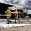 Firefighters install perimeter crime scene tape after the body of a fire victim was discovered inside the charred remains of a home at 221 E. Fourth in Lahoma, Okla. Wednesday, March 5, 2014. Rural volunteer fire departments from Drummond, Hillsdale-Carrier, Meno, Ringwood, Waukomis assisted Lahoma until the blaze was extinguished. (Staff Photo by BONNIE VCULEK)