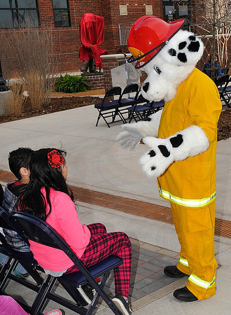 Sparky the Dog visits with Garfield Elementary students priot to a dedication ceremony for a statue of Sparky the Dog in memory of former Enid Fire Chief Phillip Clover Friday. (Staff Photo by BILLY HEFTON)