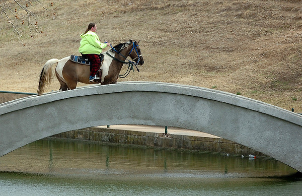 A woman rides a horse across the bridge at Government Springs Park Monday. (Staff Photo by BILLY HEFTON)