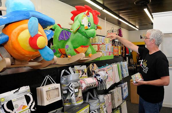 Glenn Jones straightens items in Baby Bumps Plus Thursday. (Staff Photo by BILLY HEFTON)