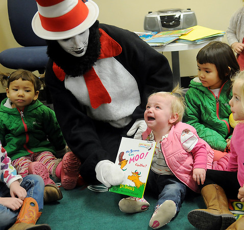 "Adelynn Stock cries as Cat In The Hat places Dr. Seuss's ""Mr. Brown Can MOO! Can You?"" on Stock's lap during Read Across America story time at the Public Library of Enid and Garfield County Wednesday, March 5, 2014. (Staff Photo by BONNIE VCULEK)"