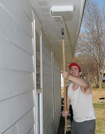 Marquette University student, Anothony Frigo, uses a roller to paint the overhang of a house being built by Habitat for Humanity Friday. (Staff Photo by BILLY HEFTON)