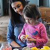 Torry Turnbow watches as her daughter, Sloan, sews a jonquil decoration for Turkey Creek School Saturday, March 8, 2014. (Staff Photo by BONNIE VCULEK)