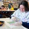 Cori Overton paints as she works on an art project with other employees at 4RKids, 710 Overland Trail, Tuesday, March 4, 2014. Several items produced by the employees are sold in the two gift shops run by the organization. (Staff Photo by BONNIE VCULEK)