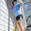 Marquette University student, Mary Wagener, paints the overhang of a house being built by Habitat for Humanity Friday. (Staff Photo by BILLY HEFTON)