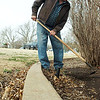 George Milacek, with the Friends of Government Springs Park, uses a hoe to remove some earlier weeds from Dillingham Garden Friday. (Staff Photo by BILLY HEFTON)