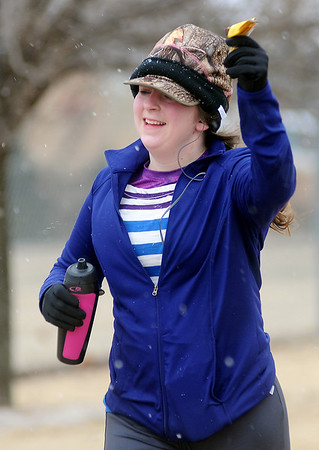 Snow falls as a runner celebrates the end of her second, 6-mile endurance loop at Groendyke Lodge during the All Day Run for Autism Saturday, March 8, 2014. Runners will continue their loops until 3 p.m. Sunday. (Staff Photo by BONNIE VCULEK)