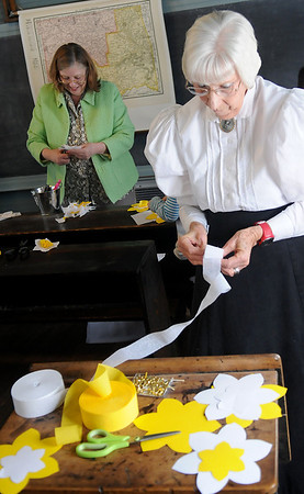 Turkey Creek School Marm Dee Taylor (right) and Karen Still (back left) create spring decorations for the Humphrey Heritage Village school Saturday, March 8, 2014. (Staff Photo by BONNIE VCULEK)