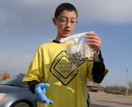 Tyler        holds a bag of cigatette butts that he pick-up at Meadowlake Park Saturday as part of the national campaign Kicks Butts Day. (Staff Photo by BILLY HEFTON)