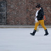 A woman walks across a sleet/snow covered parking lot at United on Willow Sunday afternoon. (Staff Photo by BILLY HEFTON)