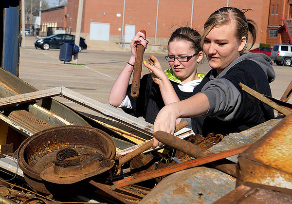 Kira Long , Brittany Hart and other members of the EHS Community Service Club and Jr. ROTC unload a trailer of scrap metal during a metal recycling drive Saturday at Enid HIgh School. (Staff Photo by BILLY HEFTON)