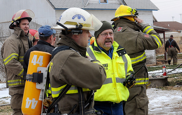 Mike Honigsberg (second from right), director of Garfield County Emergency Management, visits with firefighters as they battle a fatal house fire in Lahoma Wednesday, March 5, 2014. (Staff Photo by BONNIE VCULEK)