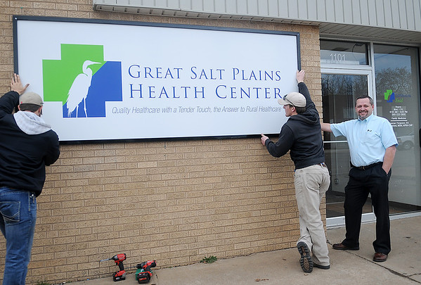 Tim Starkey (right), executive director of the new Great Salt Plains Health Center in Enid, pauses next to the new business signage at 1101 E. Broadway as Jacob McBride (left) and Jessie Kline, with Kline Signs, complete the sign installation Friday, March 7, 2014. (Staff Photo by BONNIE VCULEK)
