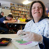 Cori Overton glances up as she paints at the 4RKids employment center Tuesday, March 4, 2014. (Staff Photo by BONNIE VCULEK)