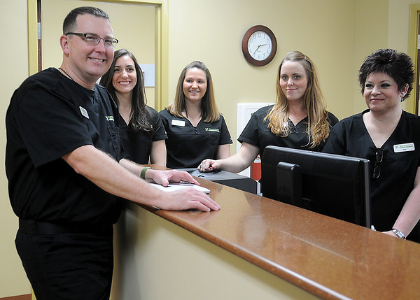Dr. Seth Switzer (left) pauses for a portrait with several Xpress Wellness Urgent Care staff members Tuesday, March 11, 2014. The new clinic in Enid, located at the site of the old Moto Photo on Van Buren, will open Wednesday. (Staff Photo by BONNIE VCULEK)