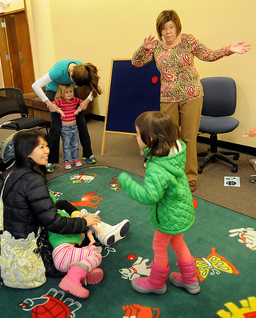 Kathy Logan (top right) leads the toddlers' music and reading during story time at the Public Library of Enid and Garfield County Wednesday, March 5, 2014. (Staff Photo by BONNIE VCULEK)