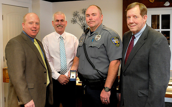 (left to right) Ryan Jackson, Enid police chief, Brian O'Rourke, Enid police officer, Mike Evans and Curt Jackson as a custom made ring from Jackson Diamond Jewelers that was presented to Enid police officer, Mike Evans, for being named Officer of the Year. (Staff Photo by BILLY HEFTON)