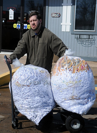 Joe Pankonin wheels shredded papers to the dumpster at 4RKids Tuesday, March 4, 2014. Workers at the 710 Overland Trail employment center shred documents for several businesses in Enid. (Staff Photo by BONNIE VCULEK)