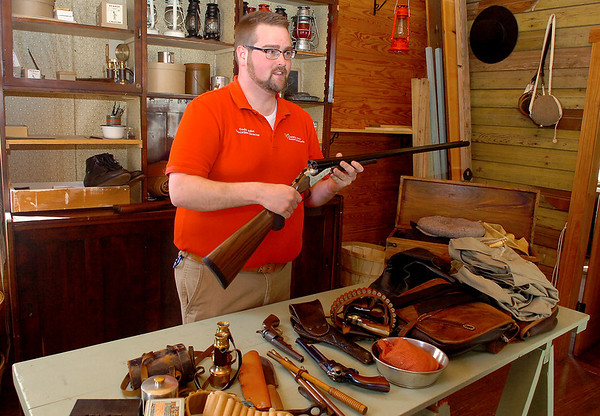 Cody Joliff, education director at the Cherokee Strip Regional Heritage Center, holds a shotgun as he talks about the April Fool's Shoot fundraiser to be held this Friday at the Grand National Gun Club. (Staff Photo by BILLY HEFTON)